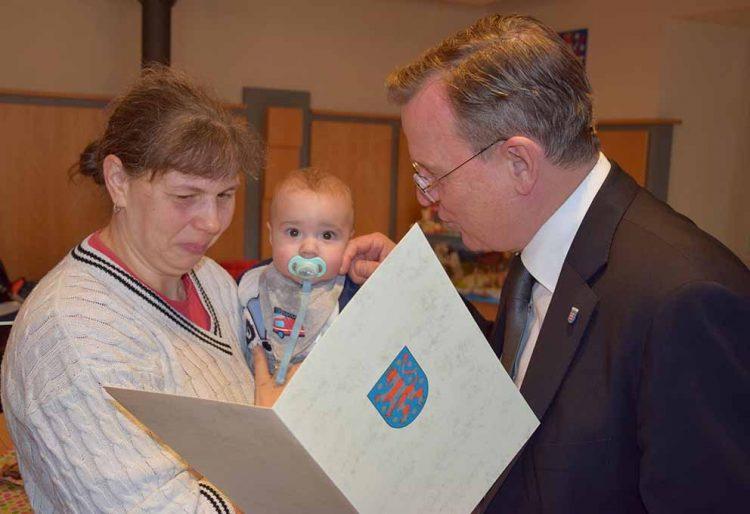 Ministerpräsident Bodo Ramelow überreicht Mandy Hüttig und Sohn Jose die Patenschaftsurkunde. | Bildquelle: © Stadt Eisenach