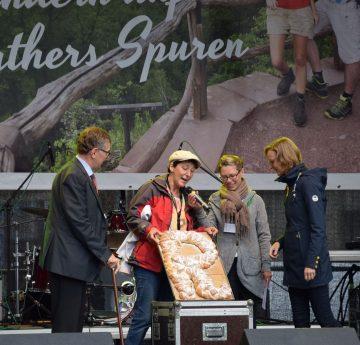 (von links): Landrat Reinhard Krebs, Christina Reißig (Rennsteigverein 1896 e.V.), Moderatorin Nicole Päsler und Oberbürgermeisterin Katja Wolf mit einem gebackenen Rennsteig-R.   Bildquelle: Stadt Eisenach