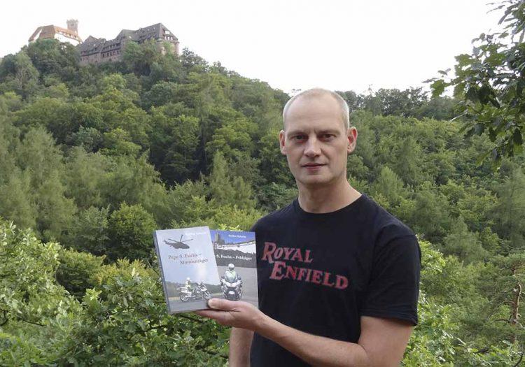 Autor Steffen Schulze mit seinen beiden Pepe-Krimis vor der Wartburg   Bildquelle: © Diana Schulze