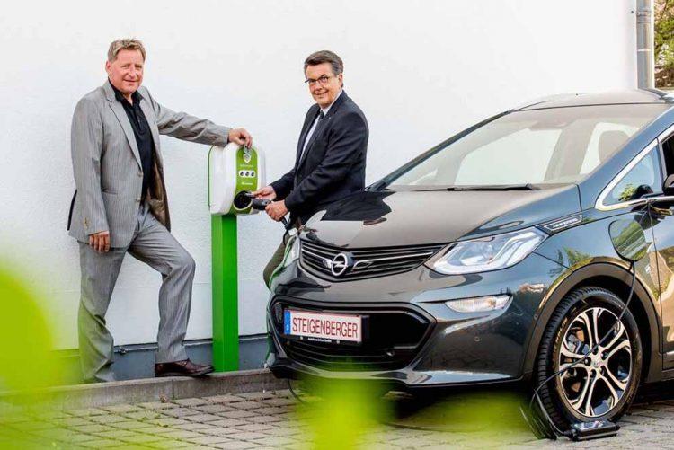 Michael Schall (Opel-Autohaus Schorr) und Hoteldirektor Dr. Hans-Joachim Hook an der neuen Ladestation | Bildquelle: © arcona Hotels & Resorts