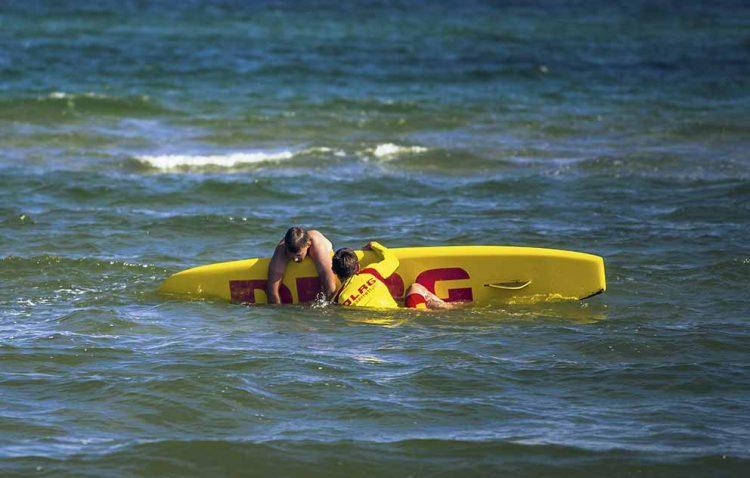 Ein Rettungsschwimmer nimmt eine verunfallte Person auf sein Rettungsbrett auf. | Bildquelle: © Arno Schwamberger / DLRG