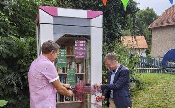 Bildquelle: © Verein Landleben Göringen-Wartha e.V.  Der stellvertretende Vereinsvorsitzende Ralf Deubner und MdL Raymond Walk schneiden das Band durch und geben den offenen Bücherschrank zur Nutzung frei.