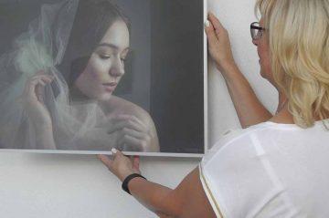 Bildquelle: © S. Blume / Landratsamt Wartburgkreis Ausstellungsorganisatorin Sabine Neubert vom Landratsamt freut sich über die gelungenen Frauenportraits von Nicole Herbst.